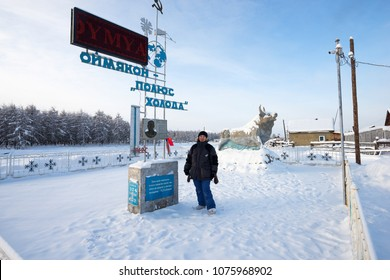Oymyakon, Yakutia - February 05 2018: A woman standing near stele in honor of the opening of the Pole of Cold in the Oymyakon. Bas-relief researcher Obruchev