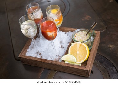 Oyster alcohol shots with sauce and lemon on wooden table