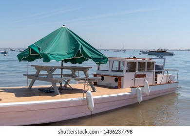 Oyster boats in the Bassin Arcachon Bay with wooden table and umbrella