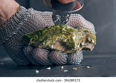 Oyster in hand with knife