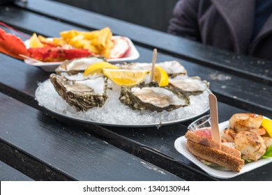 Oyster with Lemon, bread, lobster with chips serve on plate.