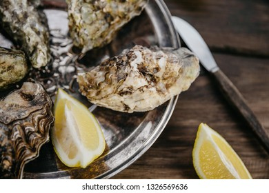 Сlosed oyster with lemon slices on a metal plate.