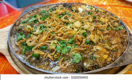 Oyster omelette or Fried clams . Thai food in hot pan with crispy flour and egg Popular manu Thai Cuisine. Delicious food on the sidewalk.