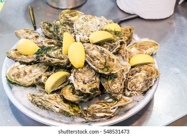 Oysters with lemon. Fresh oysters on ice with lemon close up.