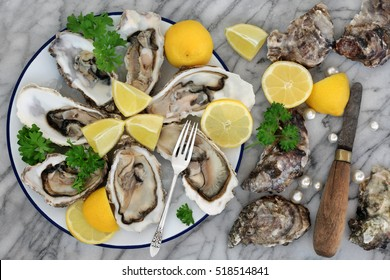 Oysters on crushed ice with antique oyster knife and silver fork with lemon fruit and pearls on a tin plate on a marble slab.