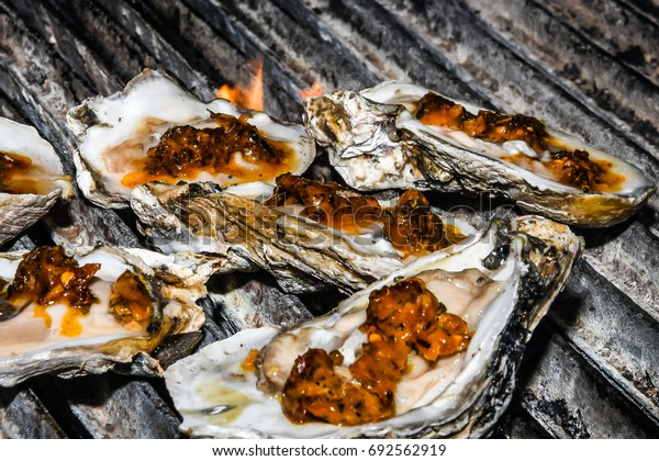 Oysters on the grill with Creole garlic butter and cheese as flames appear