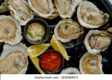 Oysters on the half shell. Fresh oysters served with garlic, shallots, cocktail sauce, mignonette sauce and fresh lemons and limes. Classic American steakhouse or French bistro appetizer.
