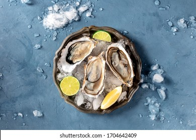 Oysters on ice, shot from the top on a slate, with lemon and lime