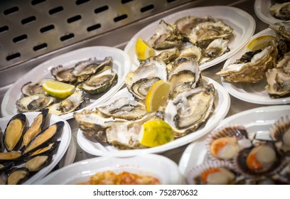 Oysters on plastic plates on seafood market