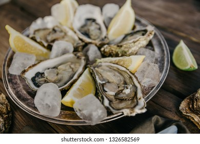Oysters plate with ice and lemon on a wooden background