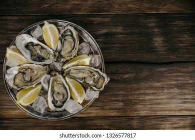 Oysters plate with ice, lemon slices, fork and brown serviette on a wooden background. Top view, copy space