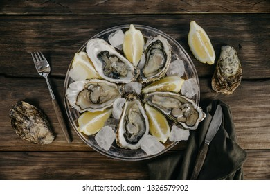 Oysters plate with ice, lemon slices, shells, fork and brown serviette on a wooden background. Top view