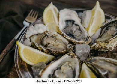 Oysters plate with ice and lemon slices, fork on a wooden background