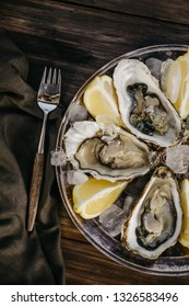 Oysters plate with ice,  lemon slices, fork and brown serviette on a wooden background. Top view