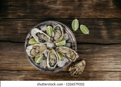 Oysters plate with ice, lime slices on a wooden background. Top view