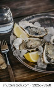 Oysters plate with lemon, fork and a glass of water on a wooden table