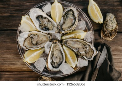 Oysters plate withice,  lemon slices, fork with a knife and brown serviette on a wooden background. Top view