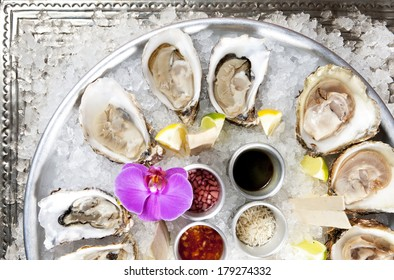 Oysters ready to serve on the silver plate with ice