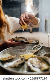 Oysters in a round metal plate with ice, lemon and a glass of white dry wine on the side, female's hand pours open lemon on oysters. Seafood restaurant