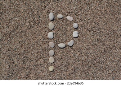 P letter made of stones on sand