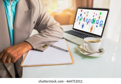 P2P lending concept.  Business man place his hand on blank paper on the table with pen, cup of coffee and laptop computer with P2P lending icons and message on screen.