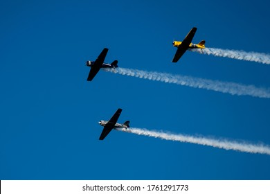 P-51 Mustangs fly over trailing smoke.