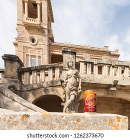 Paceville, Malta - Jun 18 2010: Focus on a can of Kinnie with a historic mansion and an ancient sculpture in the background. Maltese bittersweet soft drink brewed from bitter oranges and wormwood.
