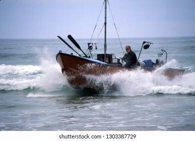 PACIFIC CITY, OREGON - MAY 30, 1996 -  Dory fisherman running his boat ashore, Pacific City, Oregon