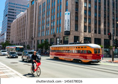 Pacific Electric Streetcar 1061, MUNI bus, vehicles and bicyclist pass Twitter headquarters on Market street - San Francisco, California, USA - July 12, 2019