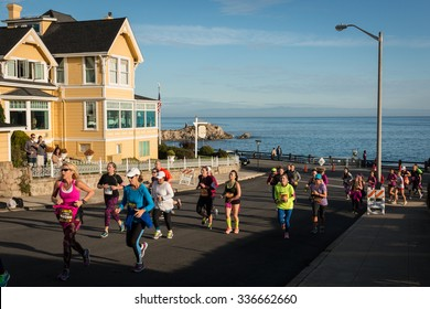 PACIFIC GROVE, CALIFORNIA, UNITED STATES, November 8, 2015: Runners climbing a hill at the Big Sur Half Marathon, with Monterey Bay in the background.