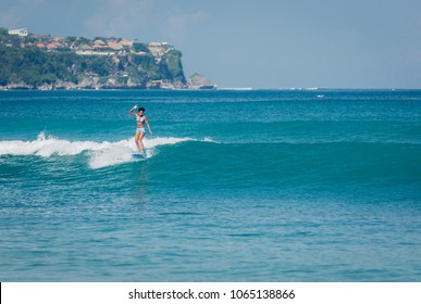 Pacific islander surfer girl with afro surfing on longboard in crystal clear blue water at Padang Padang beach, Bali, Indonesia