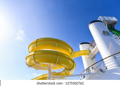 Pacific Ocean - December 10, 2018: Passengers aboard the ocean cruise liner Carnival Legend are waiting for their turn on the yellow water slide. - Image