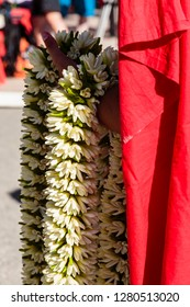 Pacific Ocean, French Polynesia, Society Islands, Huahine. Close-up shot of woman holding traditional Polynesian lei, locally called hei, made of Tahitian gardenias.