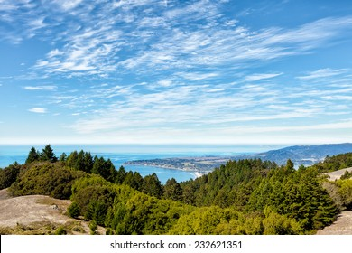 The Pacific Ocean, Stinson Beach and Bolinas viewed from a mountain path, with trees in the foreground. Location: 30 miles north of San Francisco