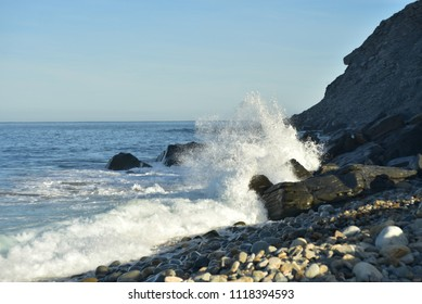 Pacific Ocean wave splashing against rock cliff shore Baja, Mexico