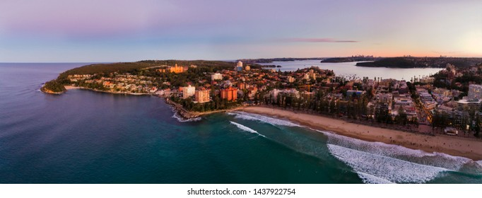 Pacific ocean waves rolling on sand of Manly beach at sunset facing waterfront and distant Sydney harbour and city CBD.