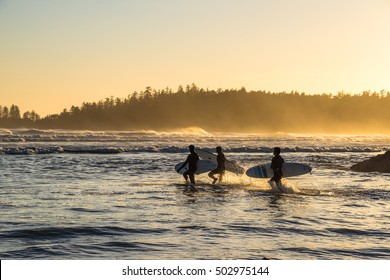 Pacific Rim National Park Reserve, BC, Canada September 22, 2016 - Surfers running out to catch some waves during sunset on Long Beach, a very popular Canadian surf mecca & vacation destination.