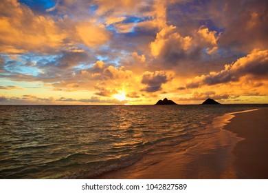 pacific sunrise through the clouds at lanikai beach, hawaii