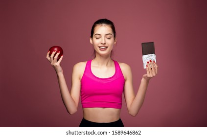 A pacified white girl in a pink sports top closed her eyes holding a red apple and chocolate in her hands. Sportswoman, fitness lady closed her eyes and holds a red apple and chocolate in her hand.