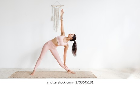 Pacified young well-groomed brunette asian woman doing stretching while standing Extended Triangle pose, Utthita Trikonasana. in a pink gymnastic suit on a white background. Place for advertising