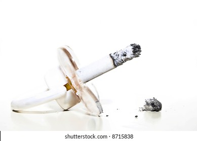 pacifier and tobacco isolated on white