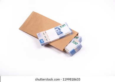 pack of 500 peso Mexican banknotes inside a paper bag, on white background