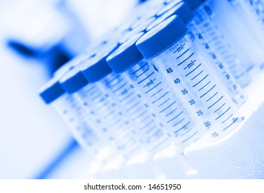 Pack of centrifuge tubes on laboratory bench.  Dynamic angle, selective focus, blue tint