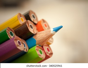 Pack of color pencils with a single sharp one symbolizing leadership concept and unique approach by standing out of the crowd group elements