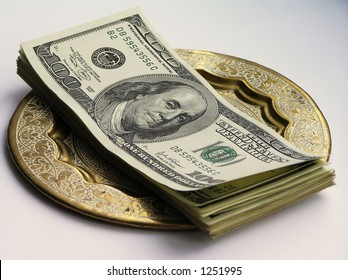 "Pack of dollar banknotes on a ""gold"" plate on a black background"