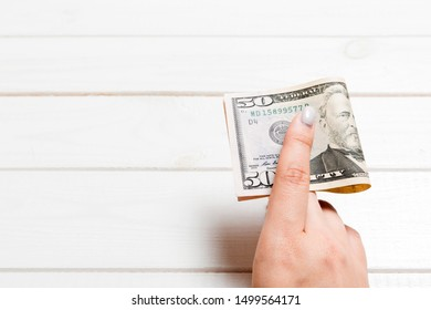 A pack of fifty dollar bills in female hand on wooden background. Salary concept with copy space.