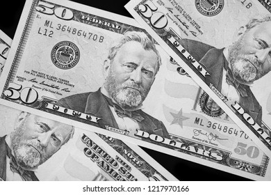 A pack of fifty dollar bills on a dark background. Black and white