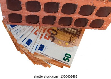 a pack of fifty-Euro notes lie under the brick