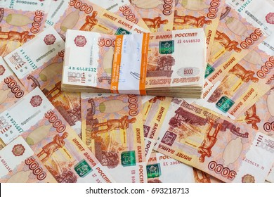 The pack of five thousandth ruble notes in half a million Russian rubles in the banking package is on the background of scattered banknotes