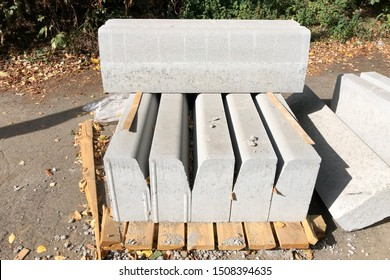 a pack of Gray Concrete road curbs on the wooden boards, outdoors. the kerbstone for concrete edging to a street or path in the rays of the summer sun.